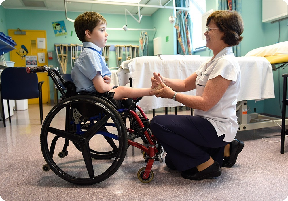 Patient in wheelchair with hospital staff - Sydney Children's Hospital Foundation