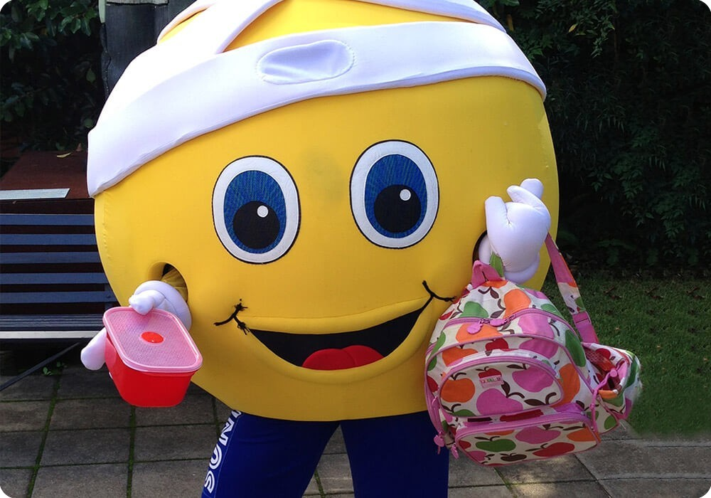 Sydney Children's Hospital Mascot, Sunny holding a lunchbox and backpack ready for school