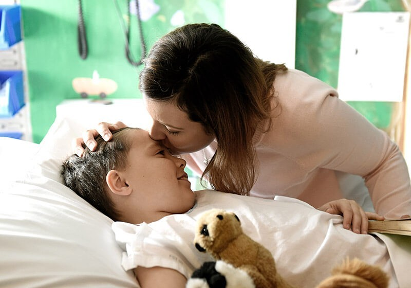 Sydney Children's Hospital patient Owen being kissed by his mother