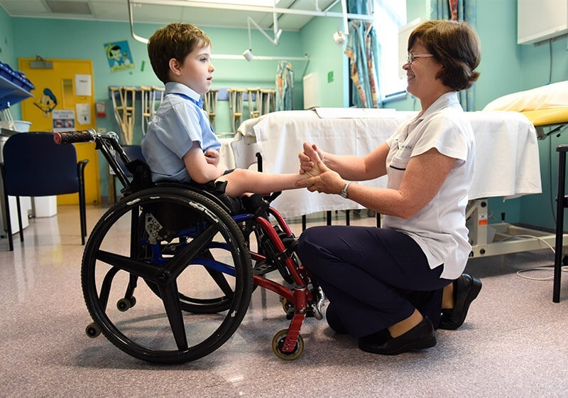 Nurse helping a patient in a wheelchair at Sydney Children's Hospital