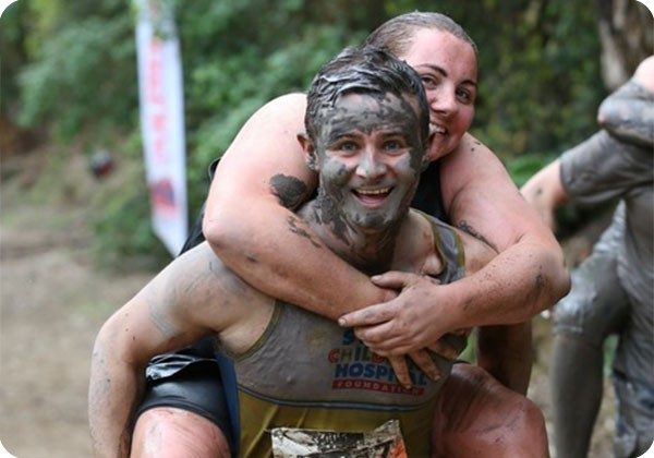Tough Mudder participant piggybacking his friend for Sydney Children's Hospital Foundation