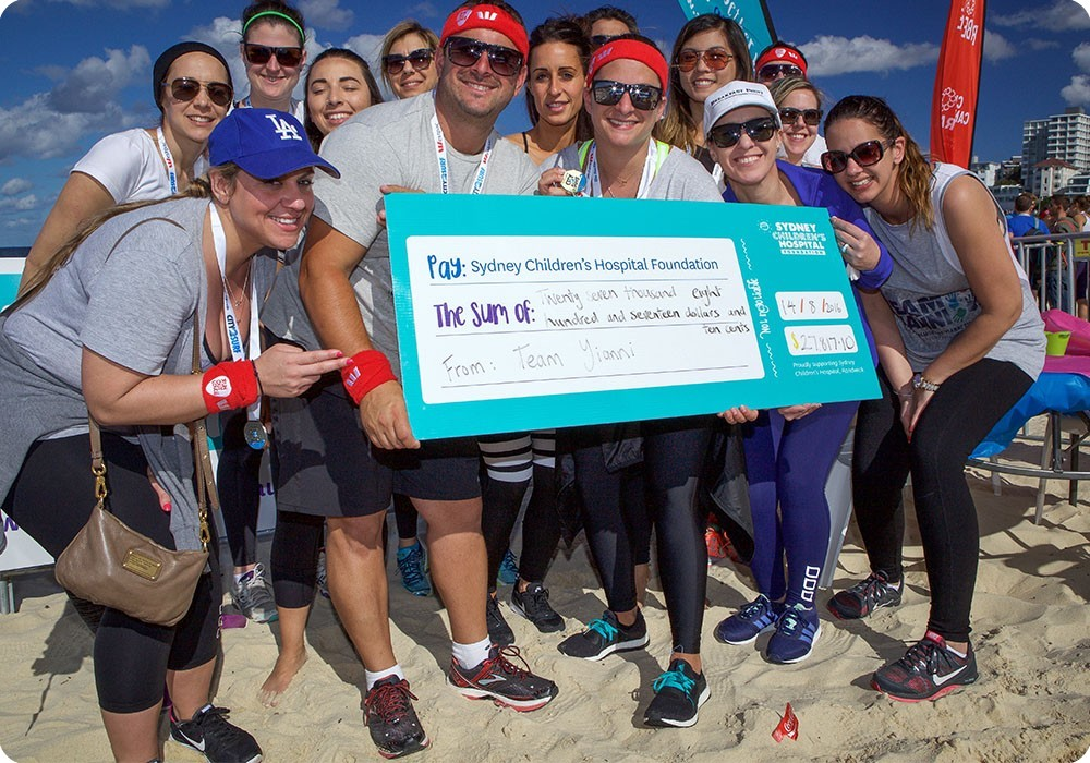 Team Kids runners holding a cheque at the end of City2surf for Sydney Children's Hospital Foundation