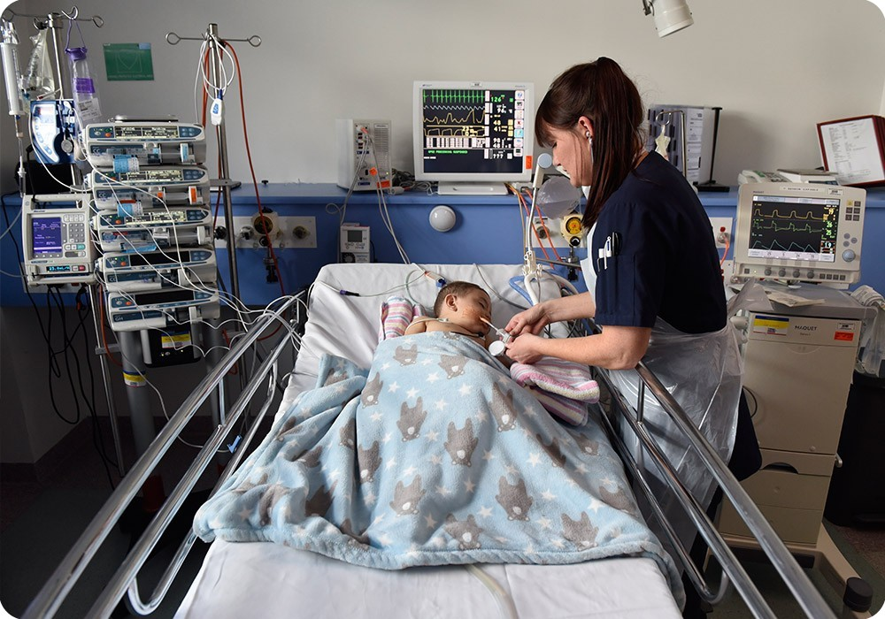 Nurse treating child on breathing support machine
