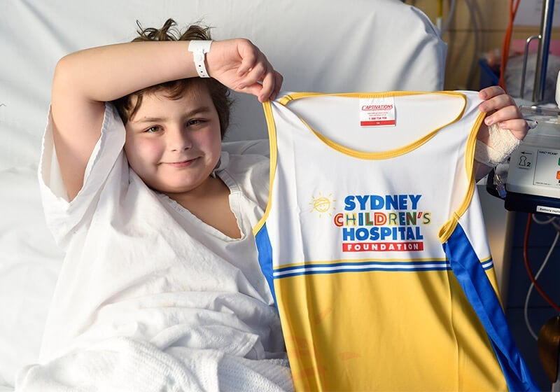 Patient holding a Sydney Children's Hospital Foundation running singlet