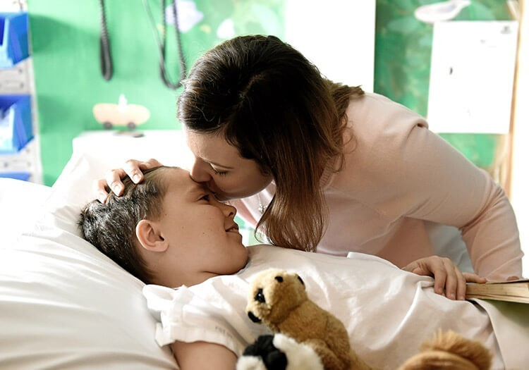Owen's mother kissing his forehead for Gold Appeal at Sydney Children's Hospital Foundation