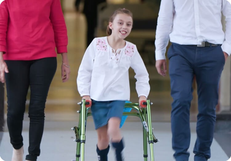Patient Coco walking through Sydney Children's Hospital, Randwick with a smile