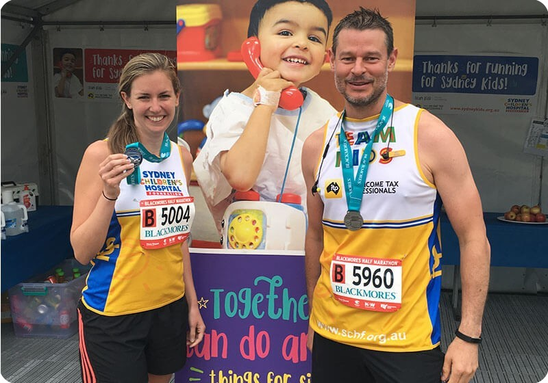 Runner Jess and Luke for Sydney Children's Hospital Foundation at the finish line of Blackmores Running Festival